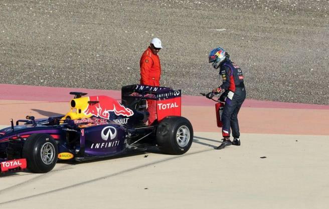 Vettel, extintor en ristre, intentando apagar un pequeño fuego en su RB10