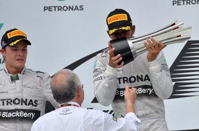 Lewis Hamilton, besando emocionado su trofeo