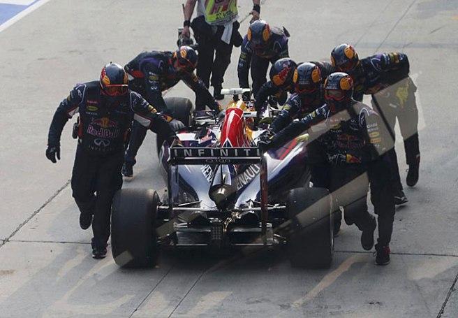 Los mecánicos de Red Bull empujando a Ricciardo de vuelta al box tras su error en el pitstop