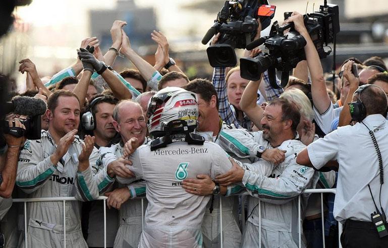Lewis Hamilton festejando con sus mecánicos su novena victoria del año