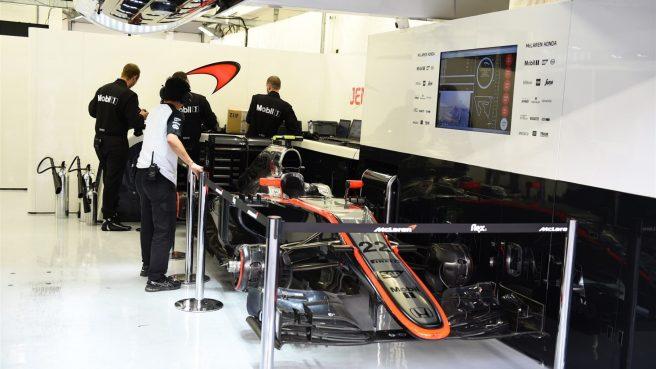 El McLaren de  Jenson Button, aparcado en el box, tras no poder tomar la salida