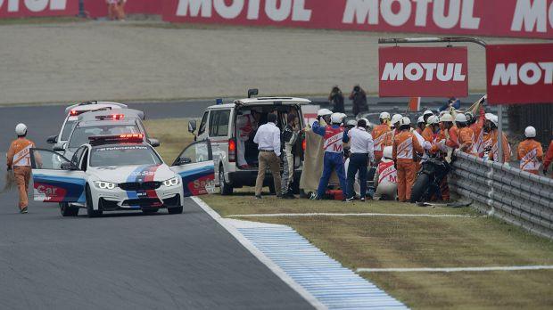 El piloto Alex de Angelis, atendido sobre la pista de Motegi tras su caída